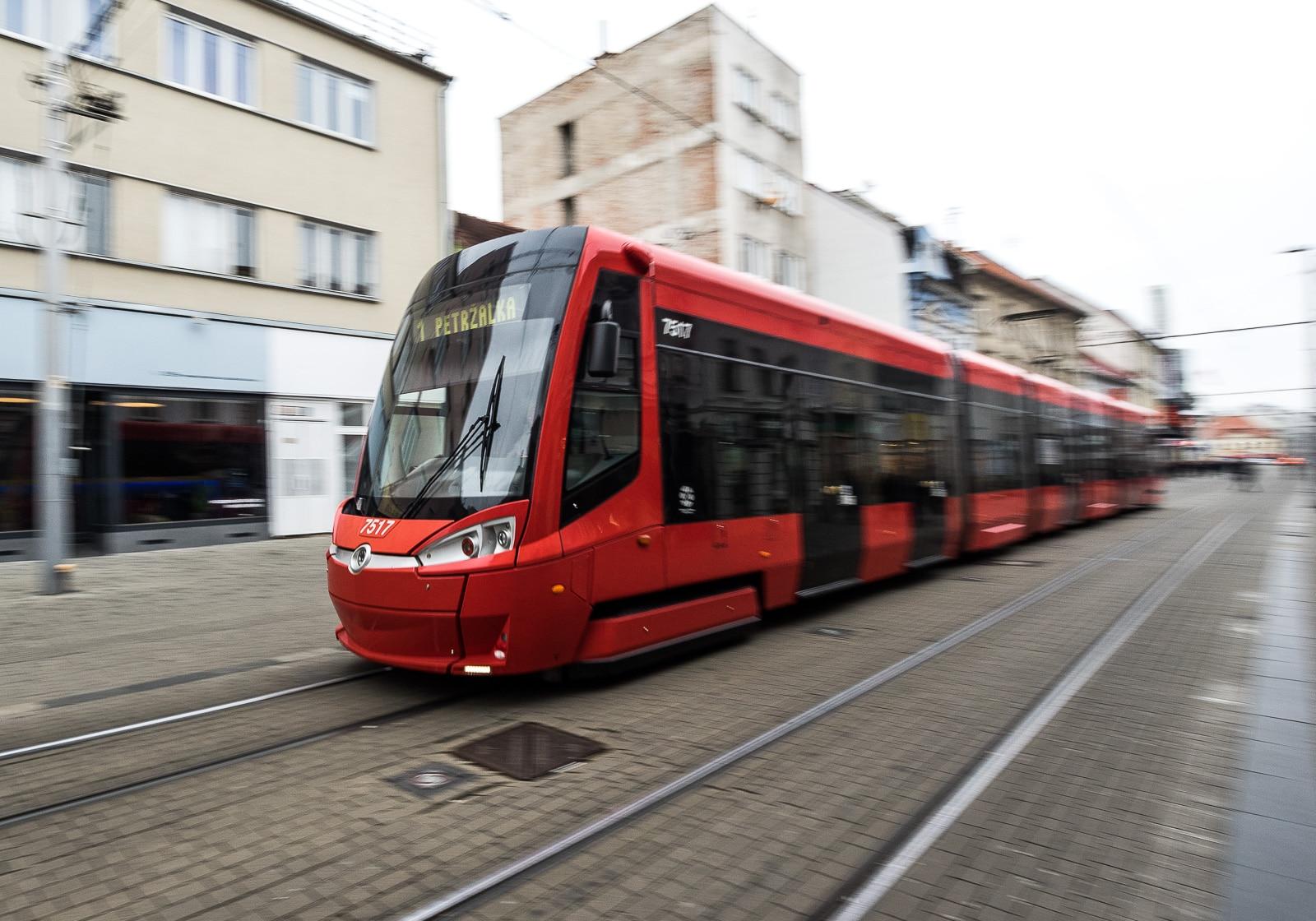 A red Skoda tram on a cobblestone street in Bratislava