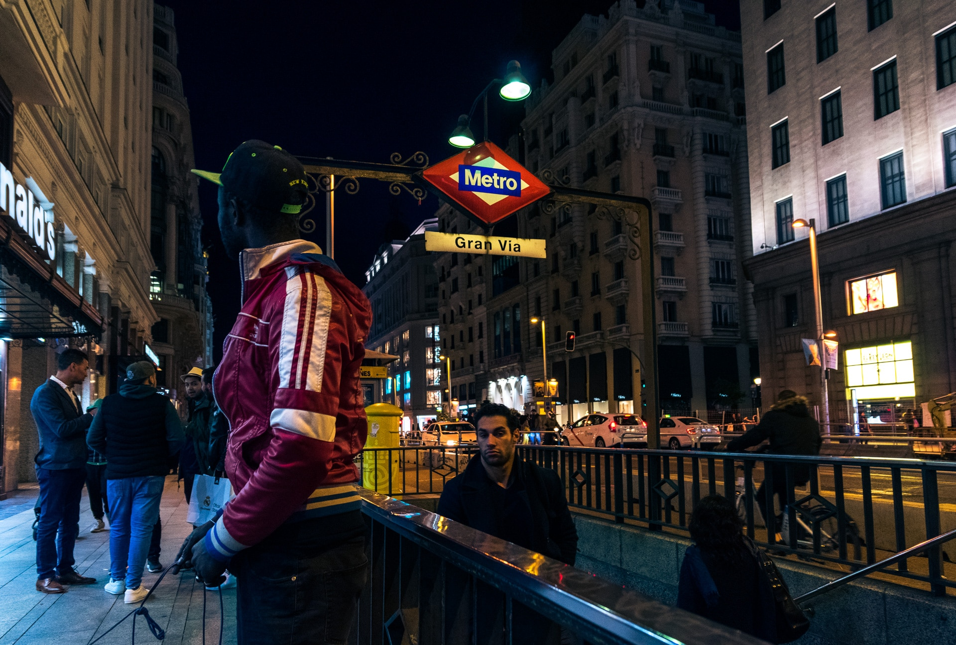 a street merchan outside the gran via metro station looking around in case the police show up