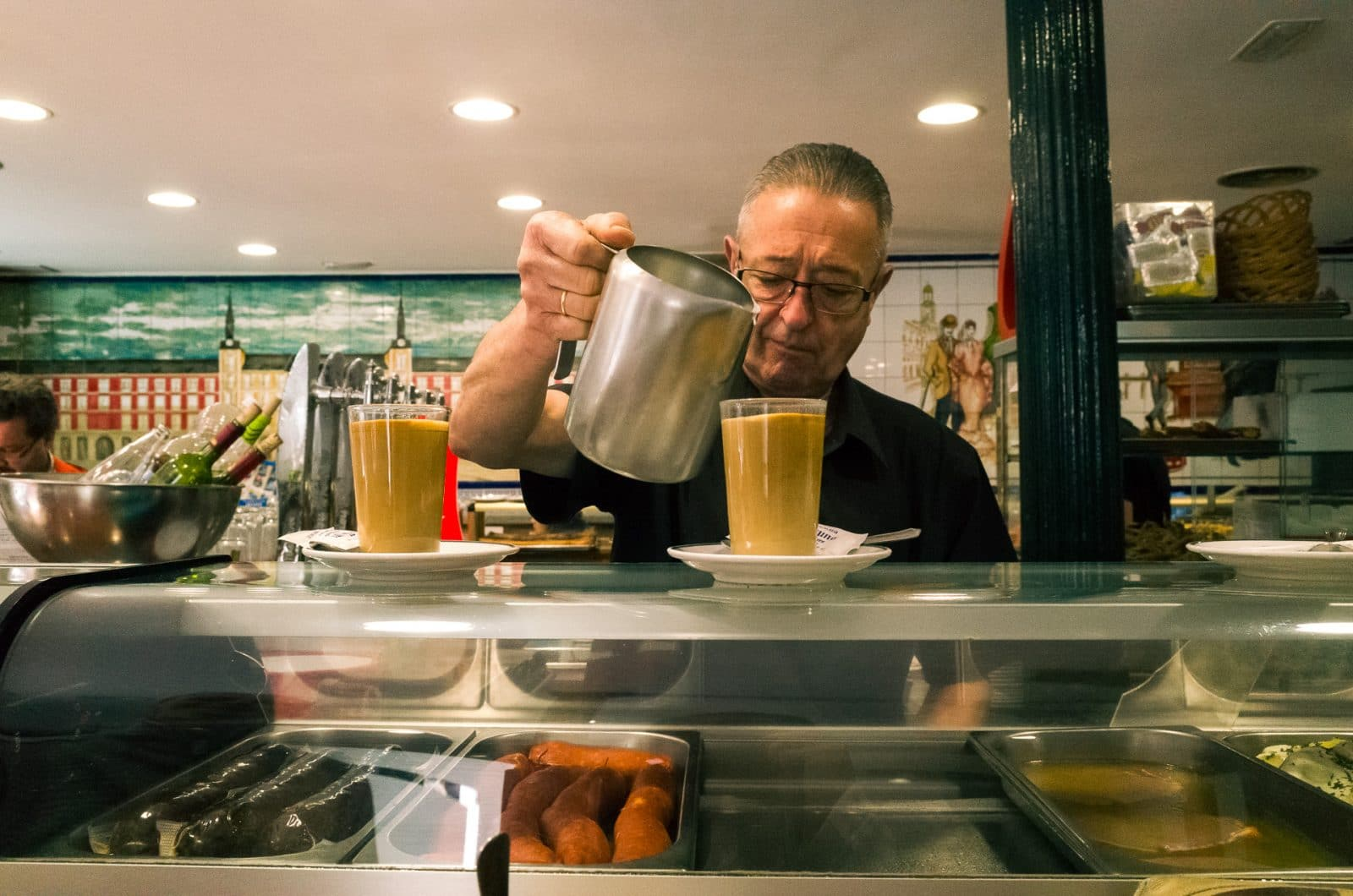Los Madrileños A guy serving coffe in a cafe
