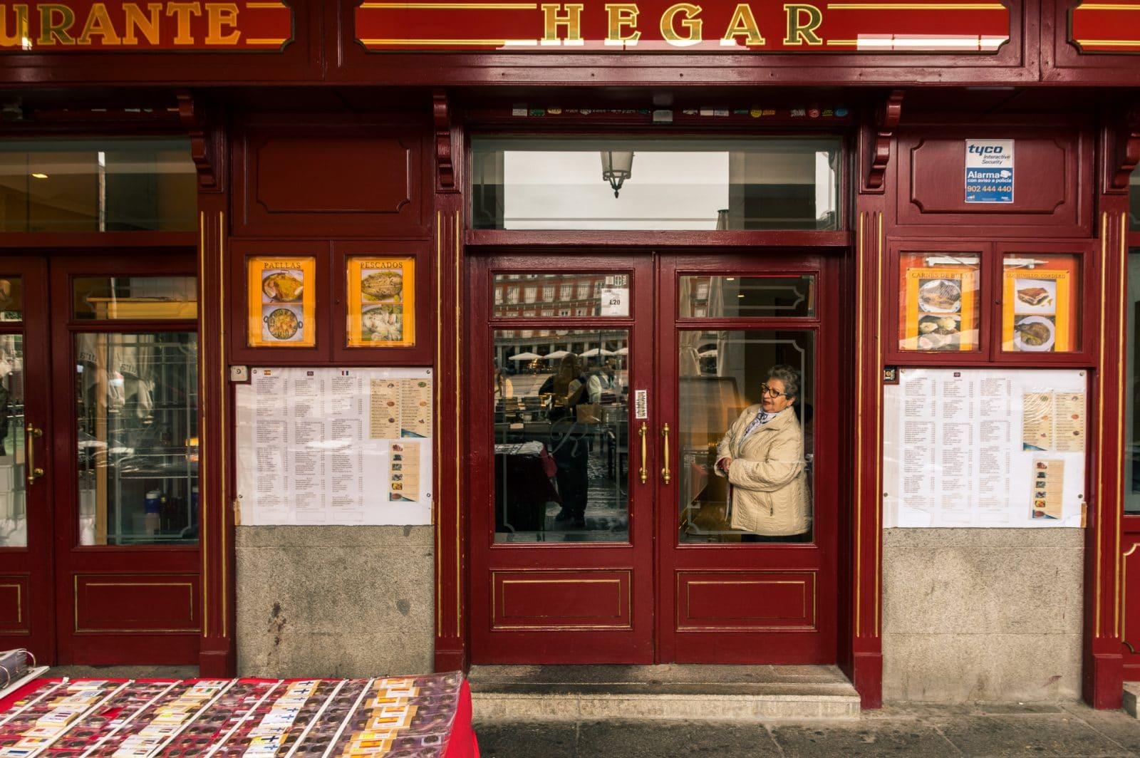 Los Madrileños woman peeking through a restaurant's door