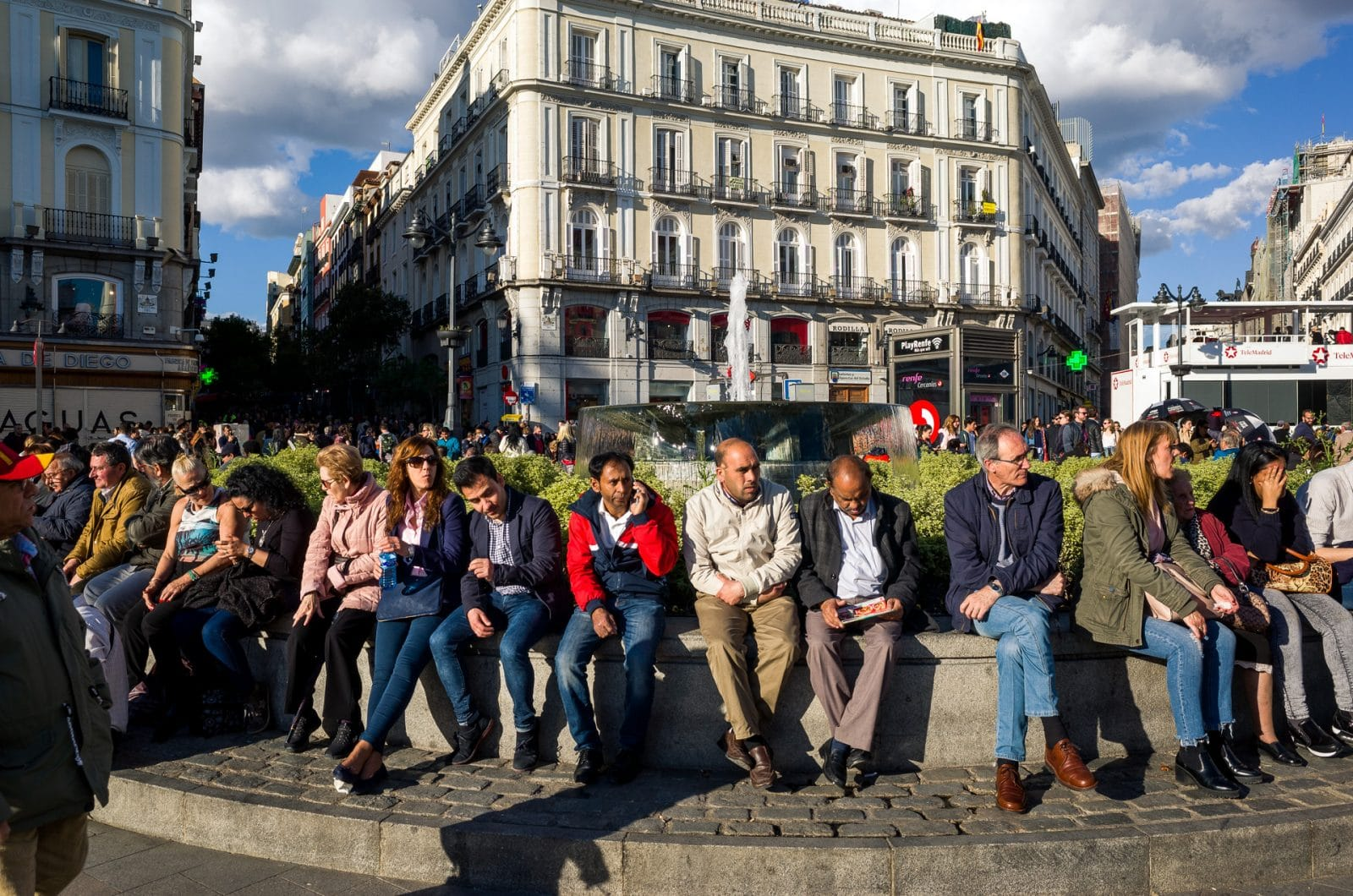 people sitting on a fountain at puerta del sol