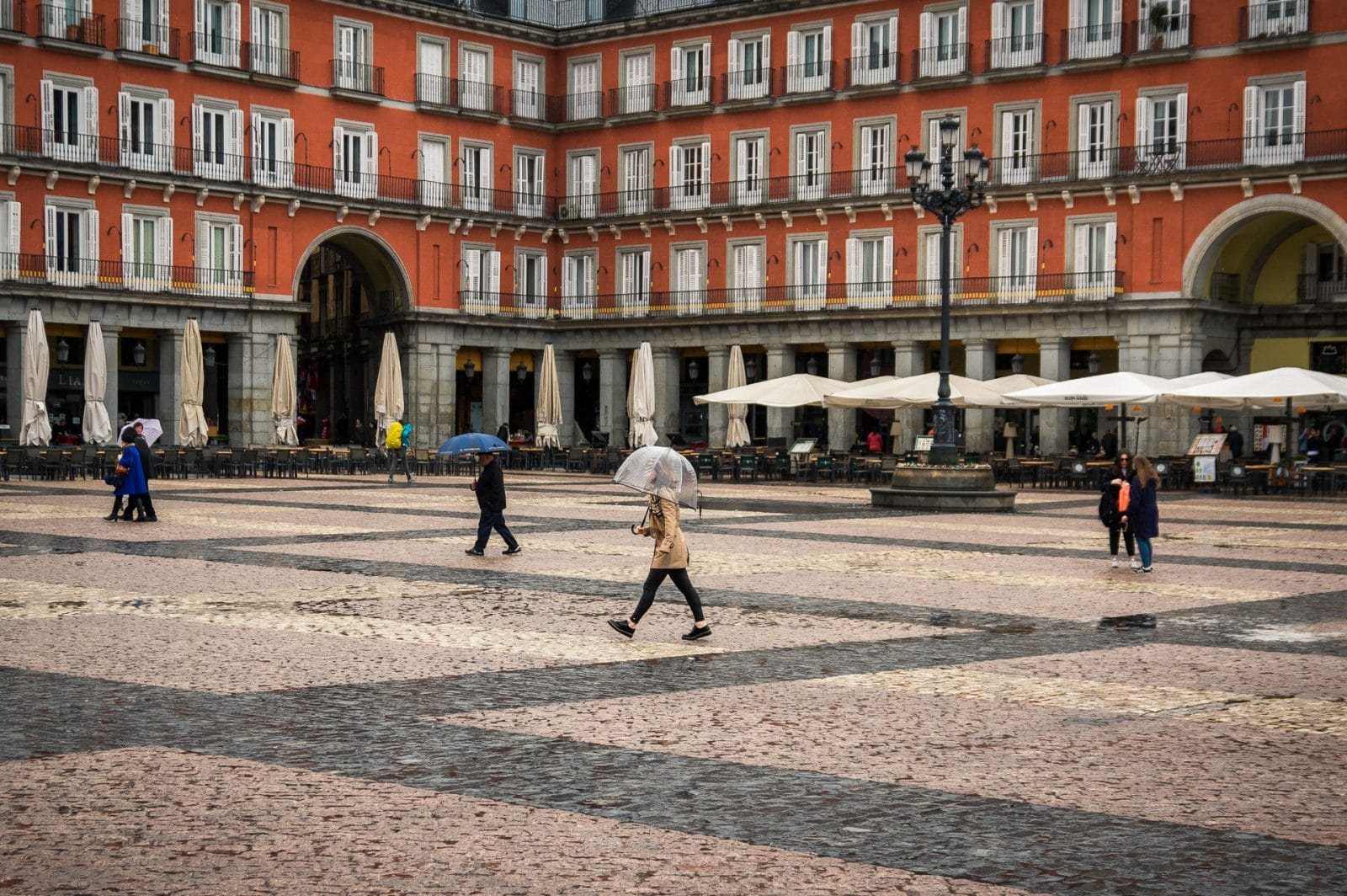 a girl walking on plaza mayor with her umbrella