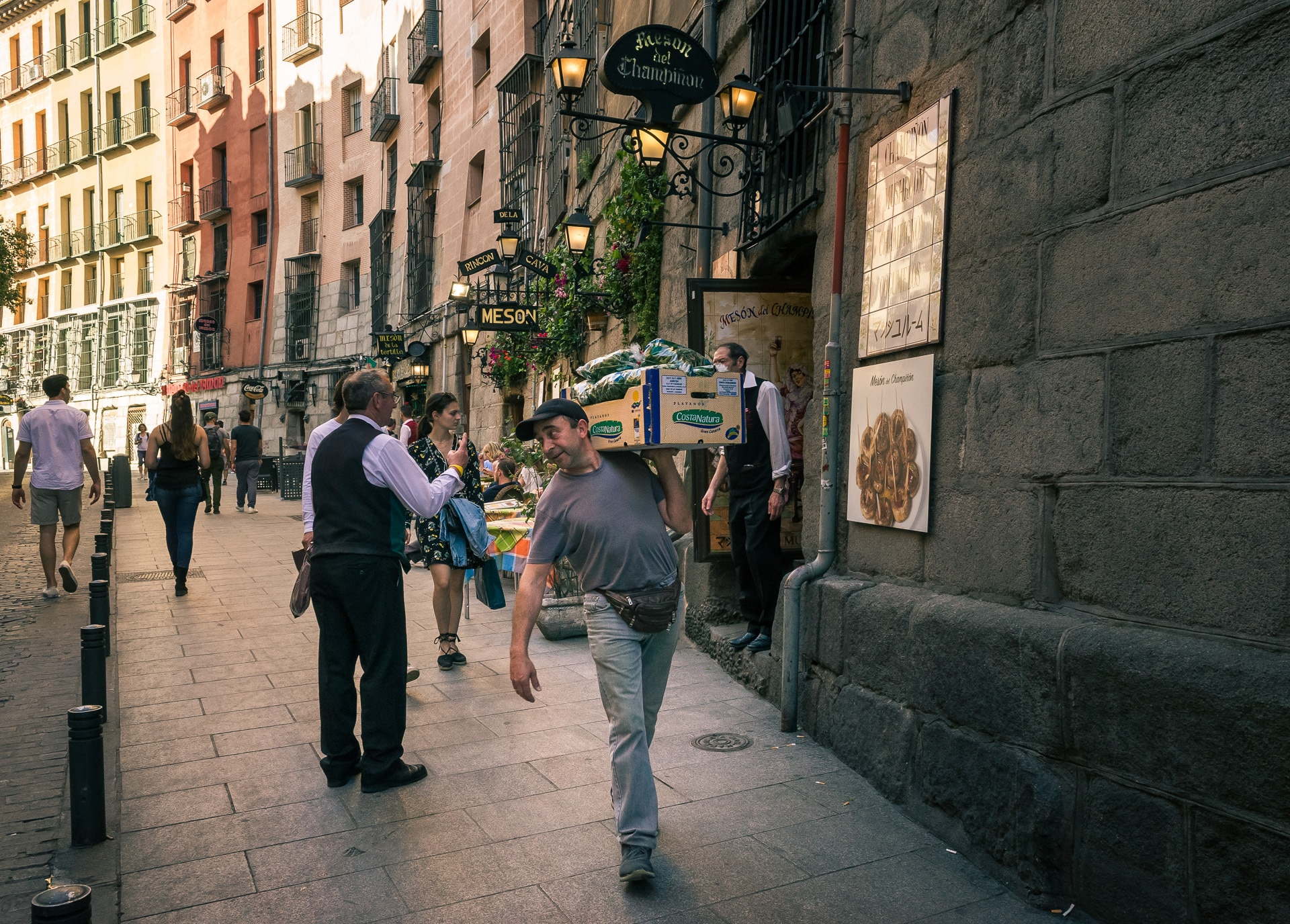 a man walking with a crate on his shoulder Los Madrileños
