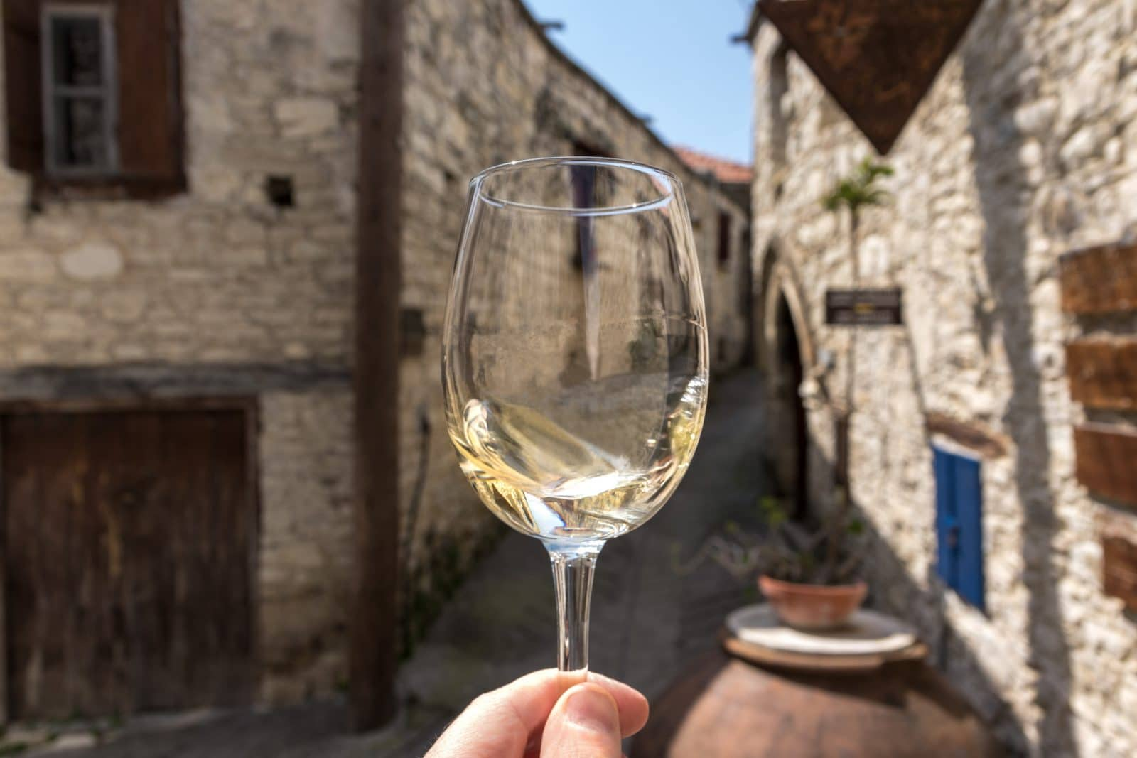 a glass of white wine with a narrow alley of Omodos village in the background