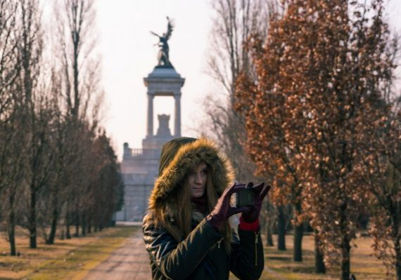 A girl shooting with the phone and the mausoleum of Lajos Kossuth on the background